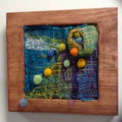 SAORI woven piece with needle felted balls in a wood stained frame
